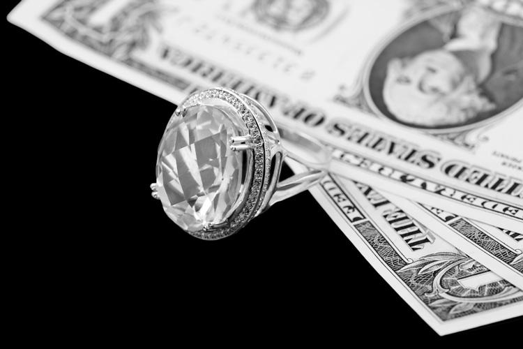 Diamond ring and dollar banknotes
