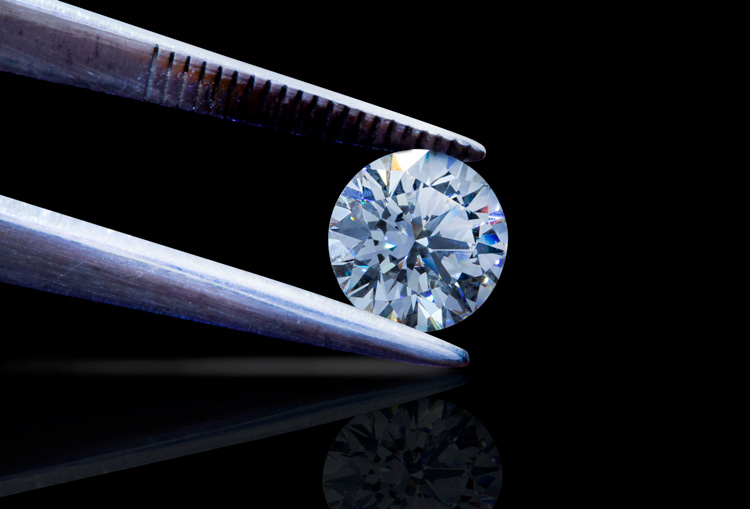 Inspecting a diamond held by tweezers