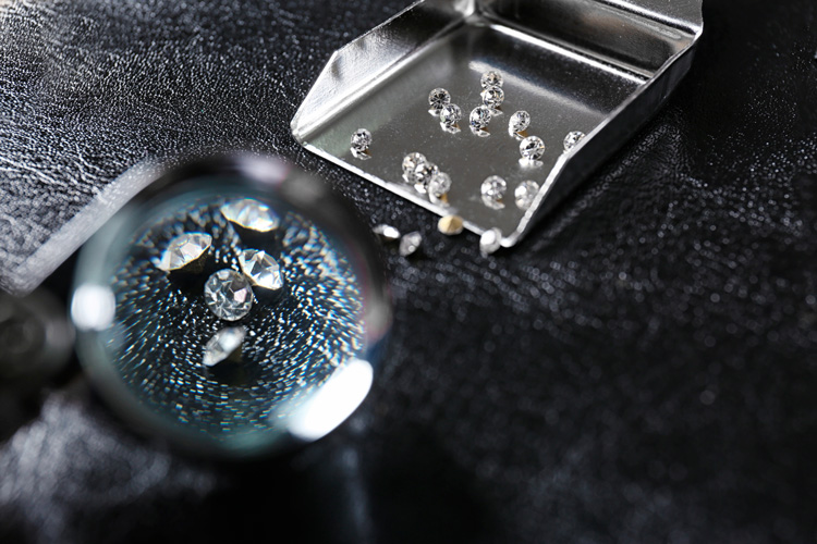 Inspecting gemstones (diamonds) under magnifying glass before buying
